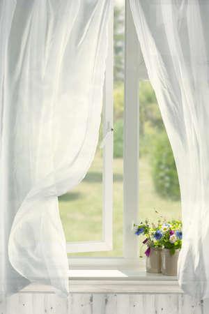Potten bloemen in landhuisvenster met golvend gordijnen