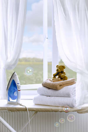 Freshly laundered towels on an ironing board with iron Stock Photo