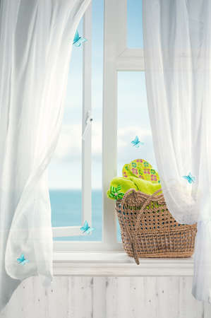 Beach basket filled with towels and flip flops with open window and billowing net curtains