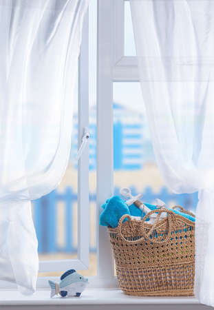 Beach basket filled with towels for the beach sitting in an open window Stock Photo