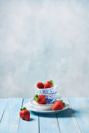 Strawberries in antique blue and white cups with sugar spoons Stock Photo