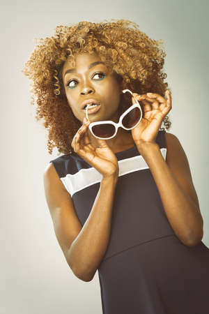 African Caribbean Woman with afro hair with vintage seventies clothing holding sunglasses Stock Photo