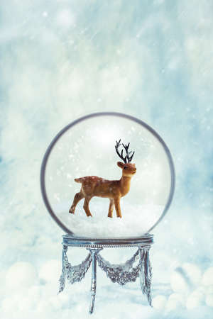 Snow globe on an antique silver stand in snowfall for Christmas holidays with reindeer figure