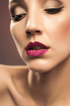 Beautiful young woman with flawless make up and glitter pink lipstick