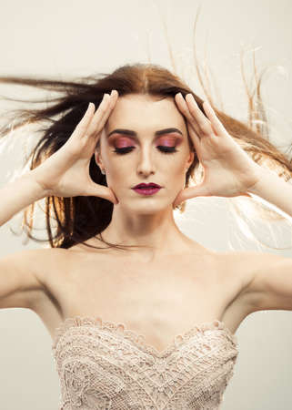 Beautiful young woman with windswept hair and eyes closing showing flawless make up