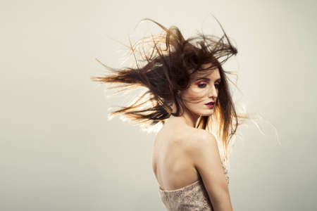 Beautiful young woman with brunette hair blowing - creative make up