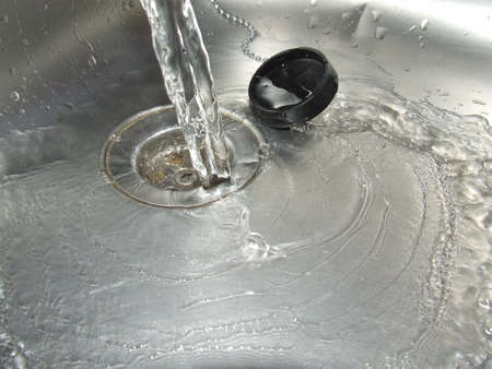 Water poured down the drain, symbolic of either flow or wastage
