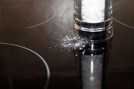 Salt spilled on reflective black surface, in acrylic grinder Stock Photo