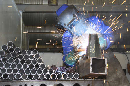 Artisan welding tubes in a production line photo