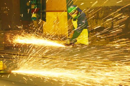 Industrial artisans grinding sheets metal