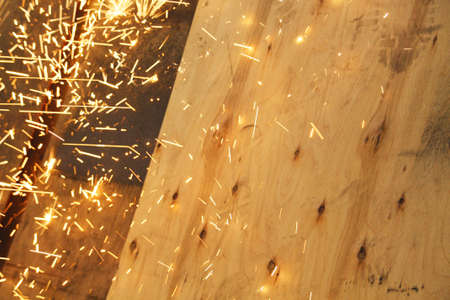 Sparks from a grinder landing on a wooden panel Stock Photo