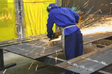 Industrial worker grinder sheets of metal photo