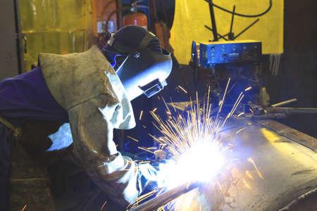 Labourer welding a custom steel tank