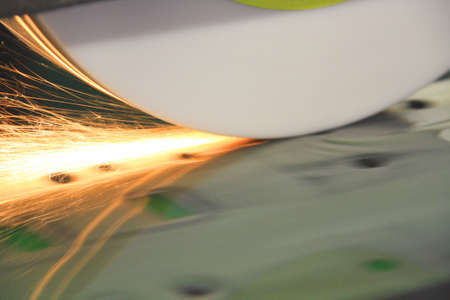 resurfacing: Grinder resurfacing a die tool made of steel showing reflection, motion blur, sparks and flares