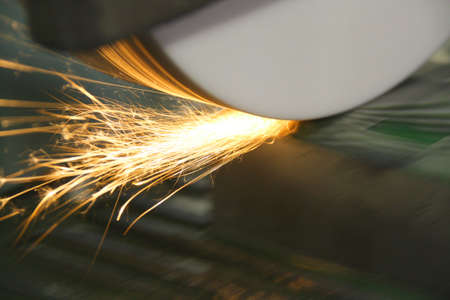 Grinder resurfacing a die tool made of steel showing sparks and flares