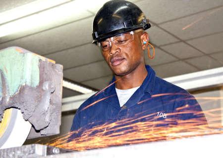 A man grinding a piece of metal