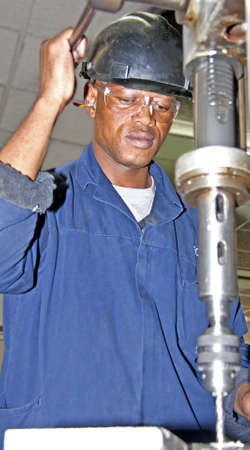 Man drilling with an industrial drill press Stock Photo