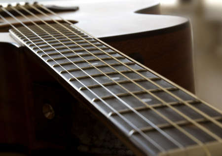 Neck of an acoustic guitar from nut to bridge Stock Photo