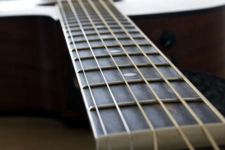 Closeup of an acoustic guitar neck and fret inlay photo