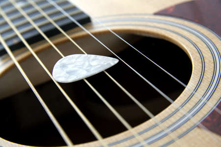 White plectrum on a 6 string acoustic guitar Stock Photo