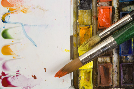 Well used artists watercolour palette and brush close up