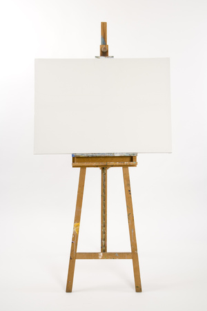 Well used artists easel with blank canvas waiting