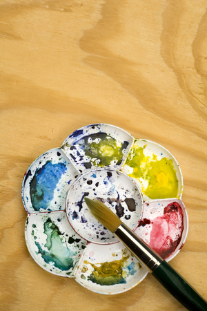 Artists flower shaped style watercolour palette and brush with copy space