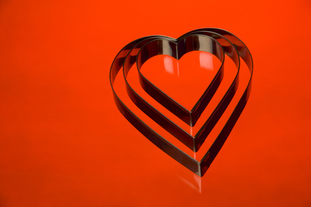 Heart shaped cookie cutters on a red background