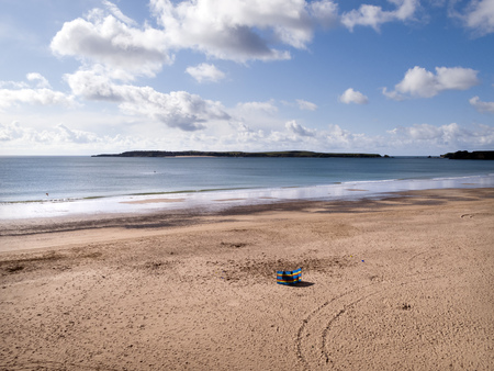 A solitary windbreak set up in early spring sunshine on South Beach, Tenby, Pembrokeshire, UK Stock Photo