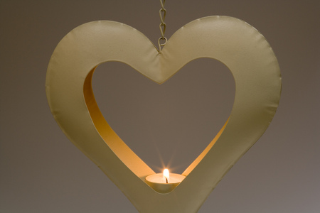 Burning tealight candle in a heart shaped metal candle holder hanging in front of a graduated plain background