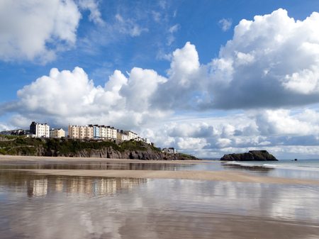 UK, Wales, Pembrokeshire, the view towards Tenby reflected in the wet sand of South Beach in glorious spring sunshine