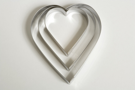 A set of three heart shaped cookie cutters on a white background Reklamní fotografie - 100896285