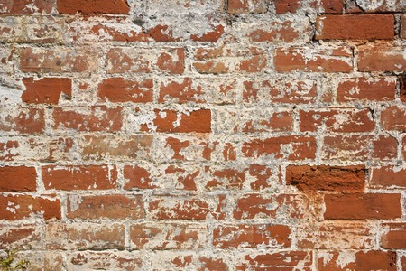 An old weathered, damaged, formerly painted, badly repaired red brick wall full frame background