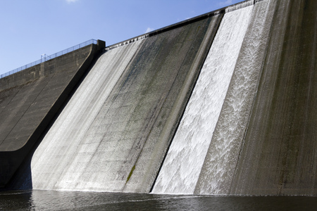White water overspill run off on the stark sunlit concrete wall of Llys y Fran Reservoir Dam, Pembrokeshire, Wales, UK Stock Photo