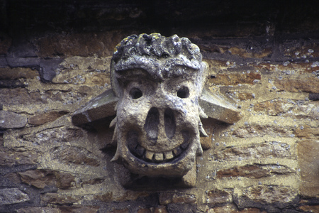 A grotesque gargoyle on the wall of an old Cotswold house, Gloucestershire, UK.