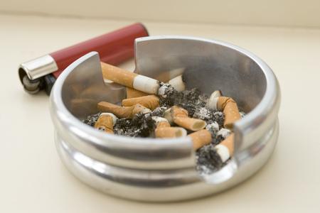Aschenbecher voller erloschener Zigarettenkippen mit einem angezündeten