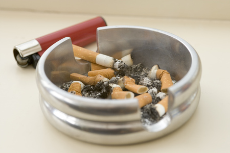 Ashtray full of extinguished cigarette butts with one lit Stock Photo