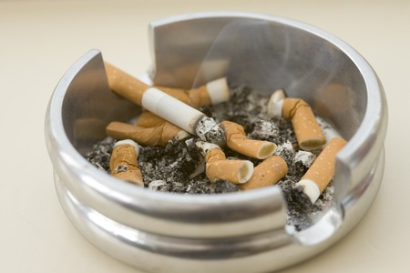 Ashtray full of extinguished cigarette butts with one lit Stock fotó