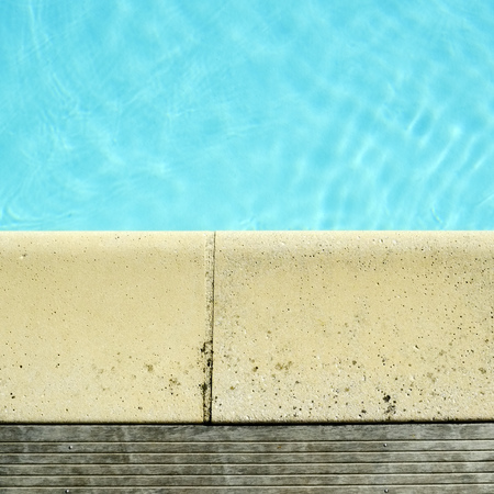 Decking and stone edging detail around a swimming pool Stock Photo
