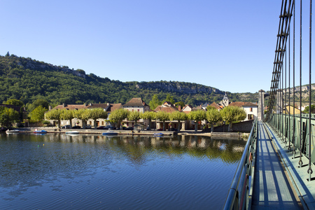 The River Lot and suspension bridge at picturesque Cajarc in the Lot Valley, Lot, Quercy, France, Europe Stock Photo