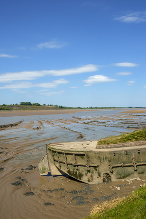 Obsolete small boats and barges were stranded on the banks of the tidal River Severn in Gloucestershire, UK to protect the river banks from erosion. Now they form an atmospheric local attraction to sightseers.
