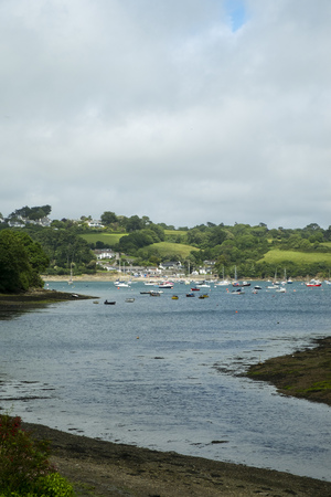 Looking across the Helford Estuary from the village of Helford at the many small boats at moorings around Helford Passage, Cornwall, UK