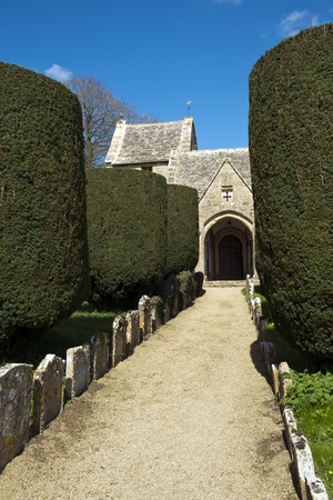 Spring sunshine on the picturesque old church and yew trees at Duntisbourne Abbots in the Cotswolds, Gloucestershire, UK