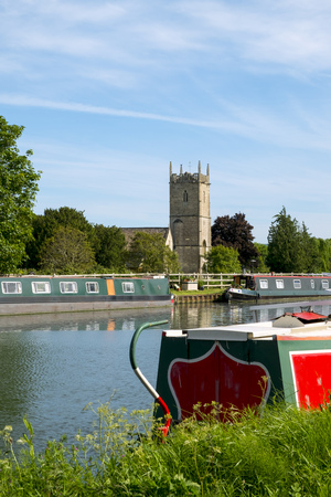 Late spring sunshine on colourful narrowboats moored near St Marys Church on the Gloucester & Sharpness Canal at Frampton on Severn, Gloucestershire, UK