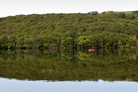 A couple pass in a canoe on Coniston Water on a dead calm early autumn morning in the Lake District, Cumbria, UK  Coniston Water, UK - 15th September 2011: Two people pass in a red canoe on Coniston Water on a dead calm early autumn morning in the Lake District, Cumbria, UK. Boats can be hired from the lakeside, with various sizes of boat for hire, from small canoes and kayaks to large personal craft.