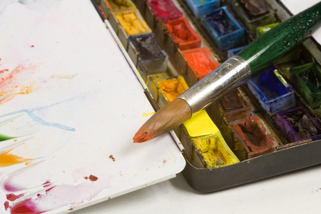 Well used artists watercolour paint palette and paint brushes Stock Photo