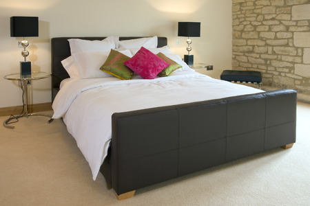 Contemporary leather covered double bed with bedside tables and lamps