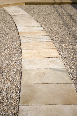 Curving stone slab path through chippings leading to deck