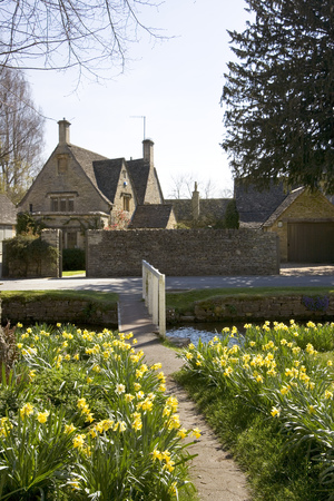 Cotswold cottage and the River Eye in spring sunshine, Lower Slaughter, Gloucestershire, UK