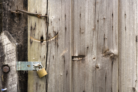 Old weathered shed door and modern unlocked padlock Stock Photo
